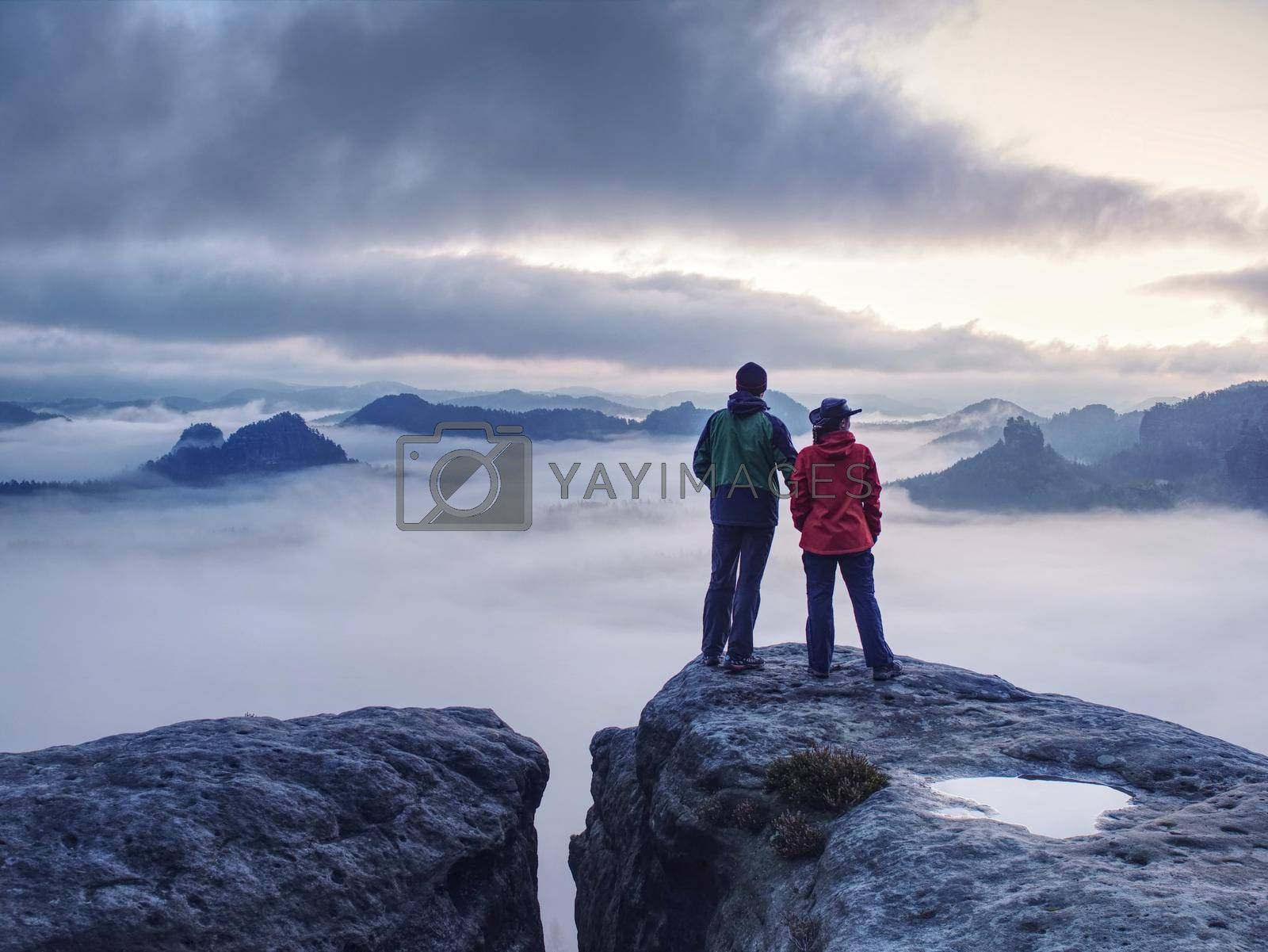 Romantic date in misty mountains. Man shows girlfriend something interesting in far distance.