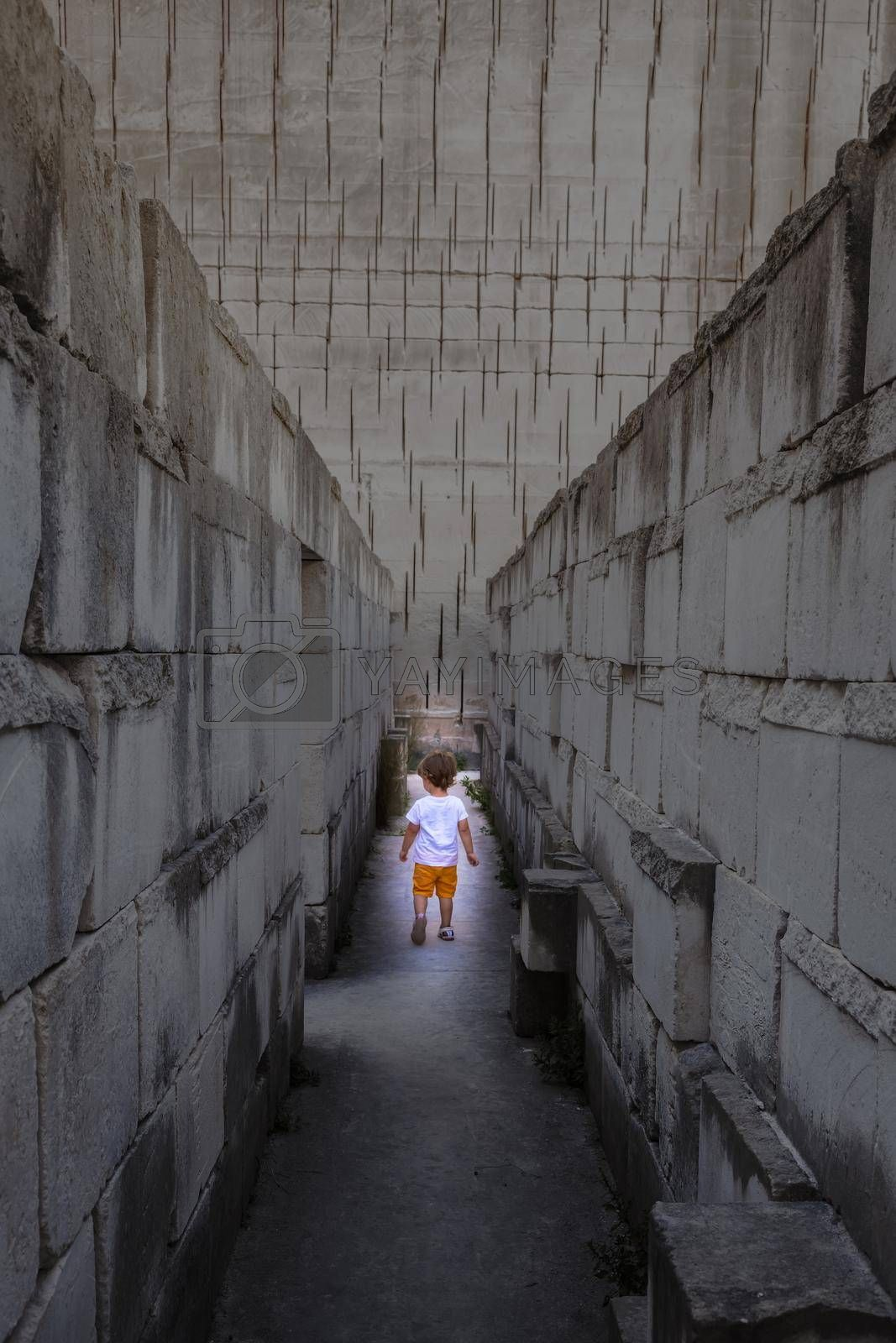 Royalty free image of Caucasian young kid walking in a labyrinth. Conceptual image for dangerous situation during childhood. by Perseomedusa
