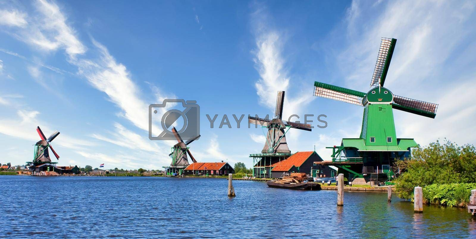 Royalty free image of Dutch windmill in green countryside close to Amsterdam, Netherlands, with blue sky and river water. by Perseomedusa