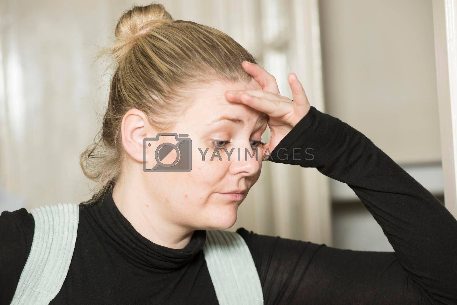 woman with headache looking annoyed and holding her head with her hand