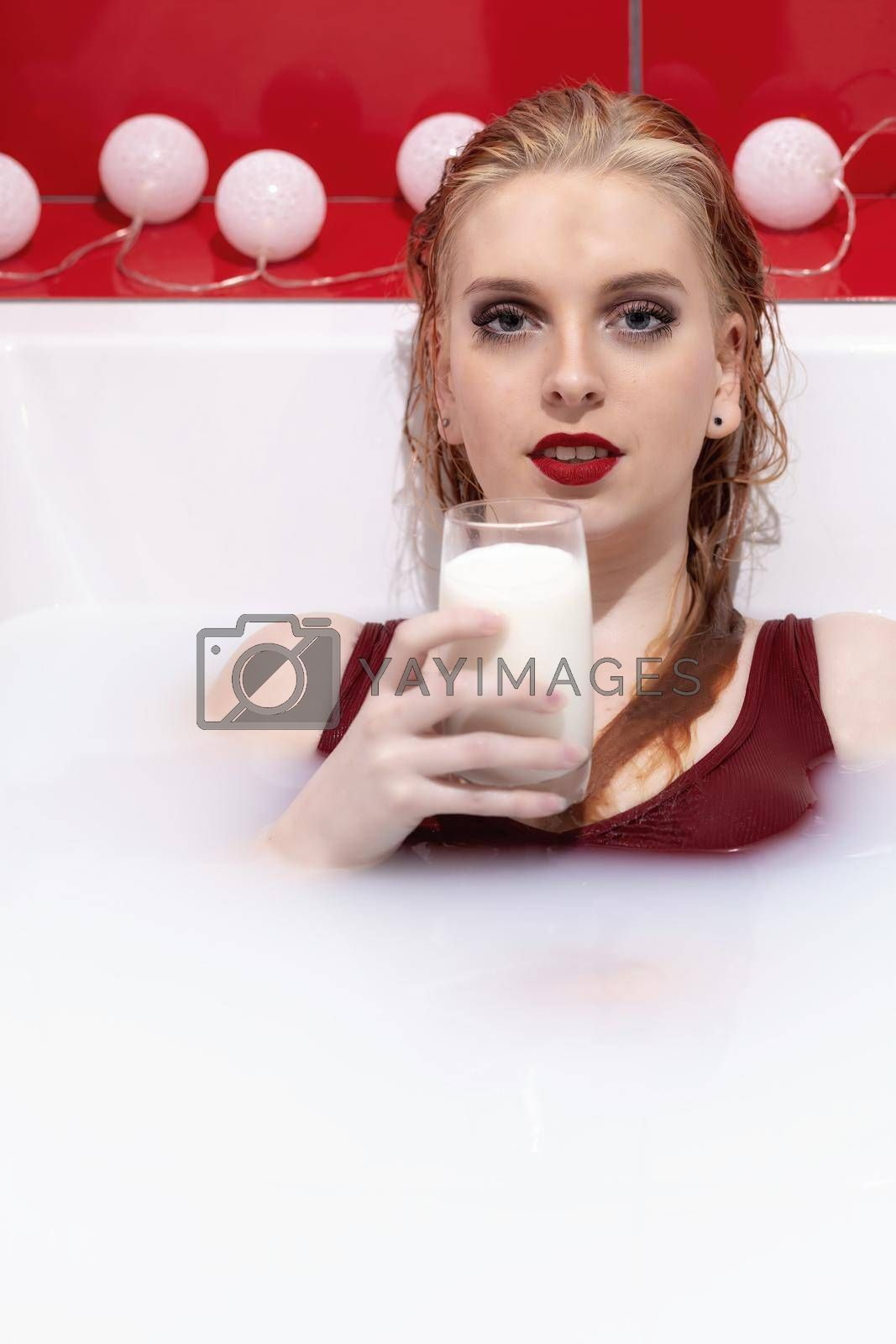 Royalty free image of Beautiful redhead young woman with red lips lying in milk bath is holding glass of milk. by Frank11