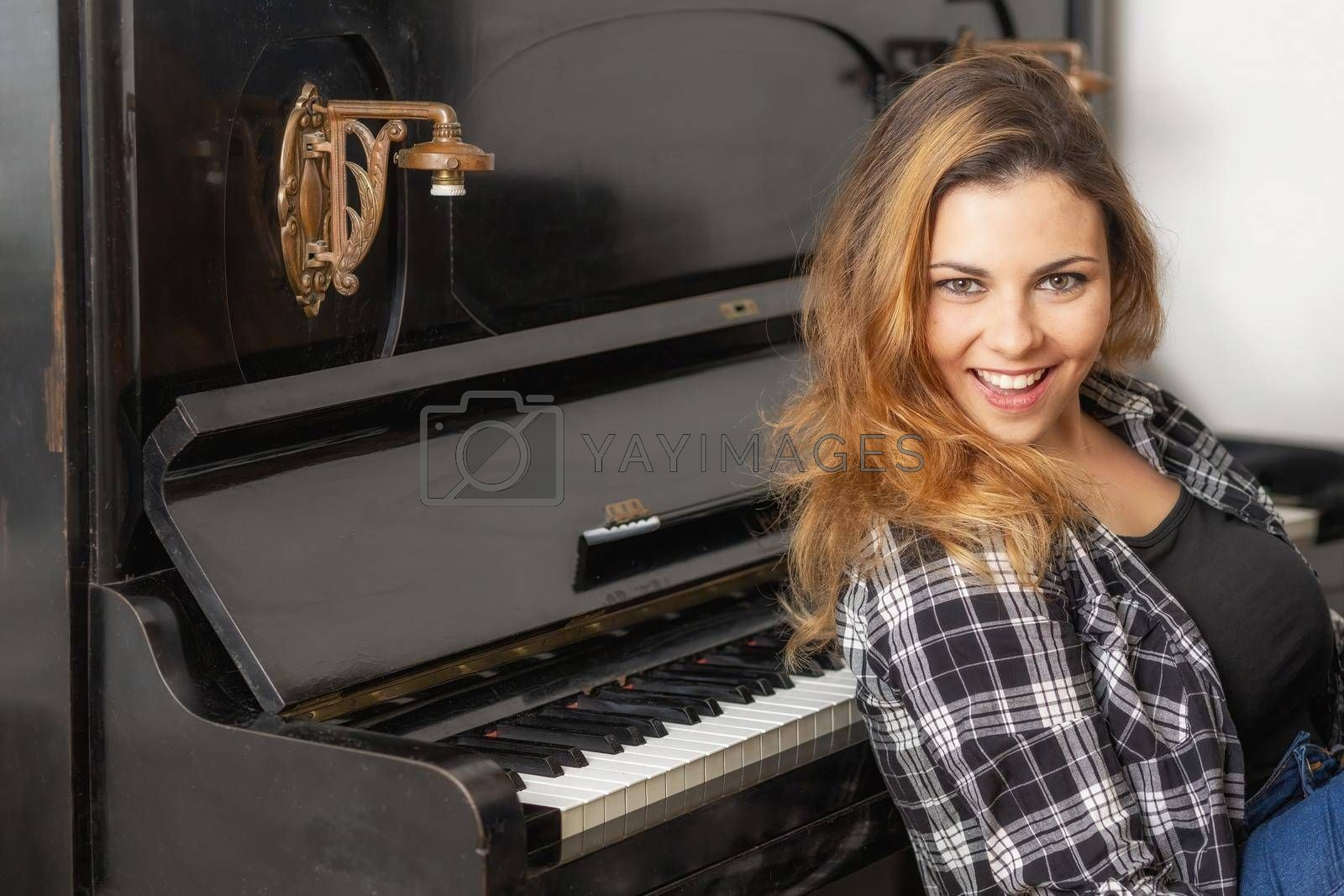 Royalty free image of Portrait of attractive young woman posing at the piano. by Frank11