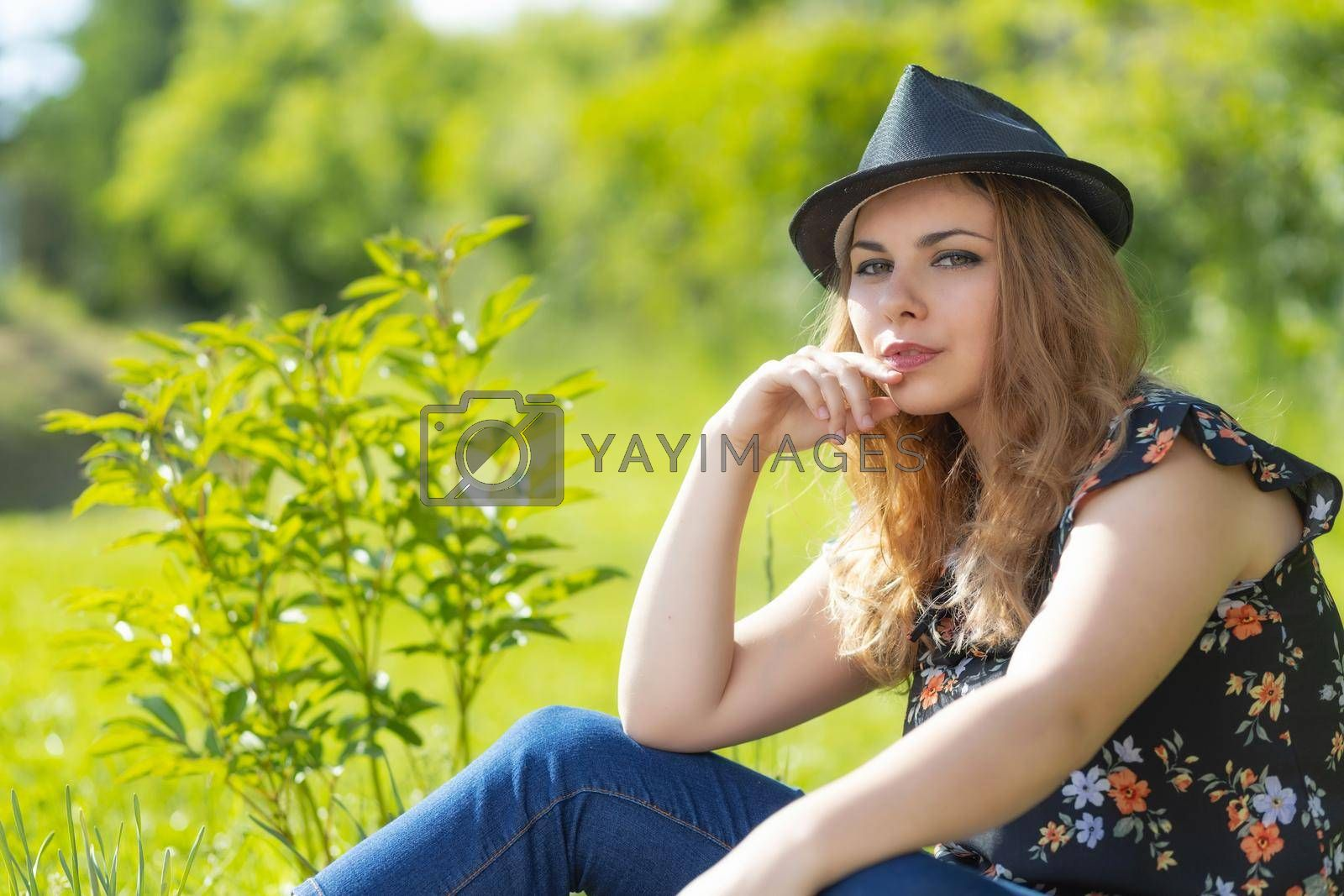 Royalty free image of Portrait of beautiful young woman posing in hat outdoors. by Frank11