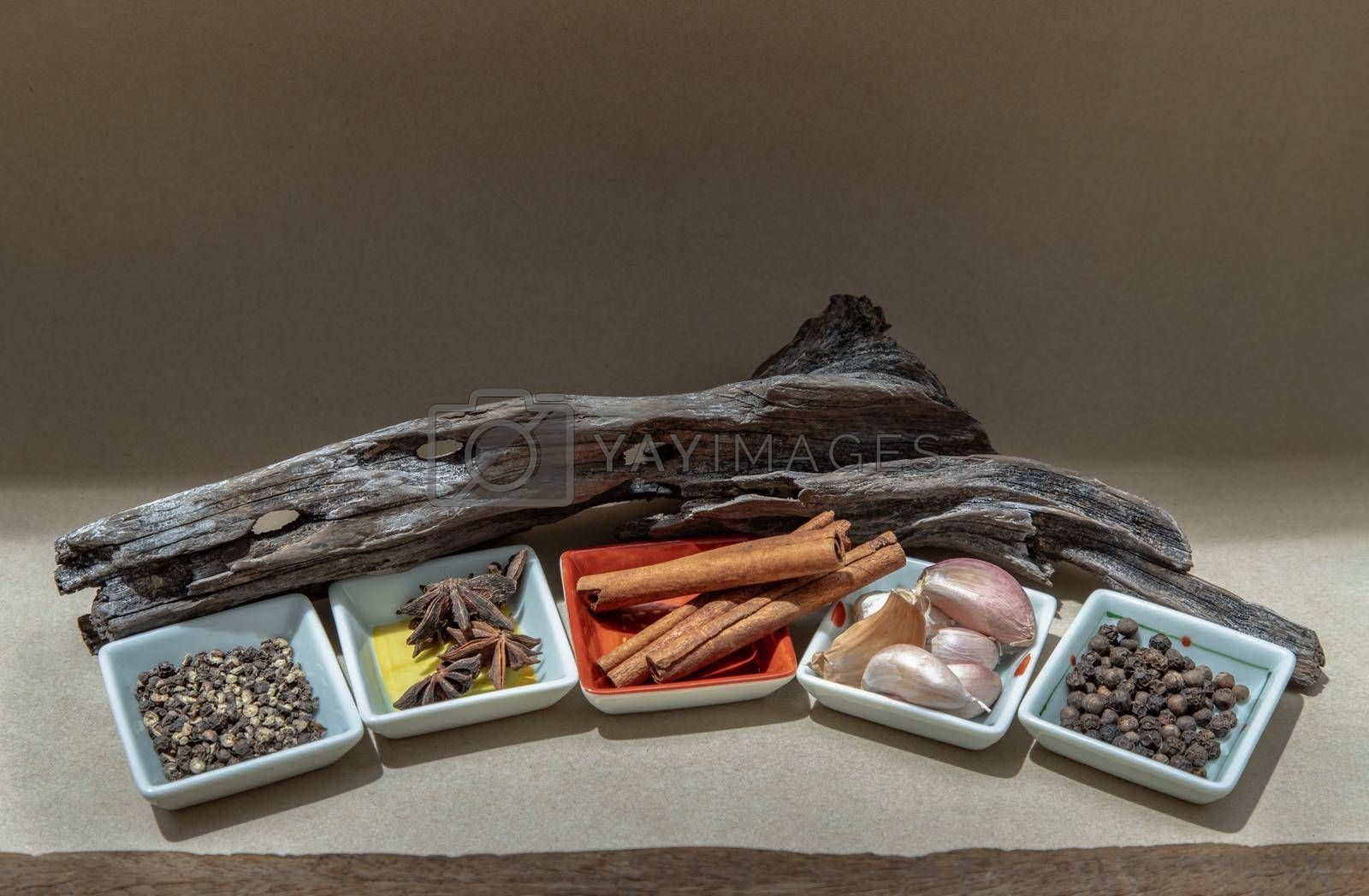 Spices and herbs seasoning containing cinnamon, star anise, garlic and black pepper in ceramics bowls on brown background. Organic herbal and healthy concept. Selective focus.
