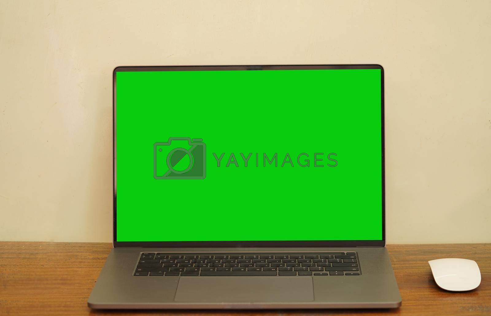 A green screen laptop and a mouse placed on a long desk.