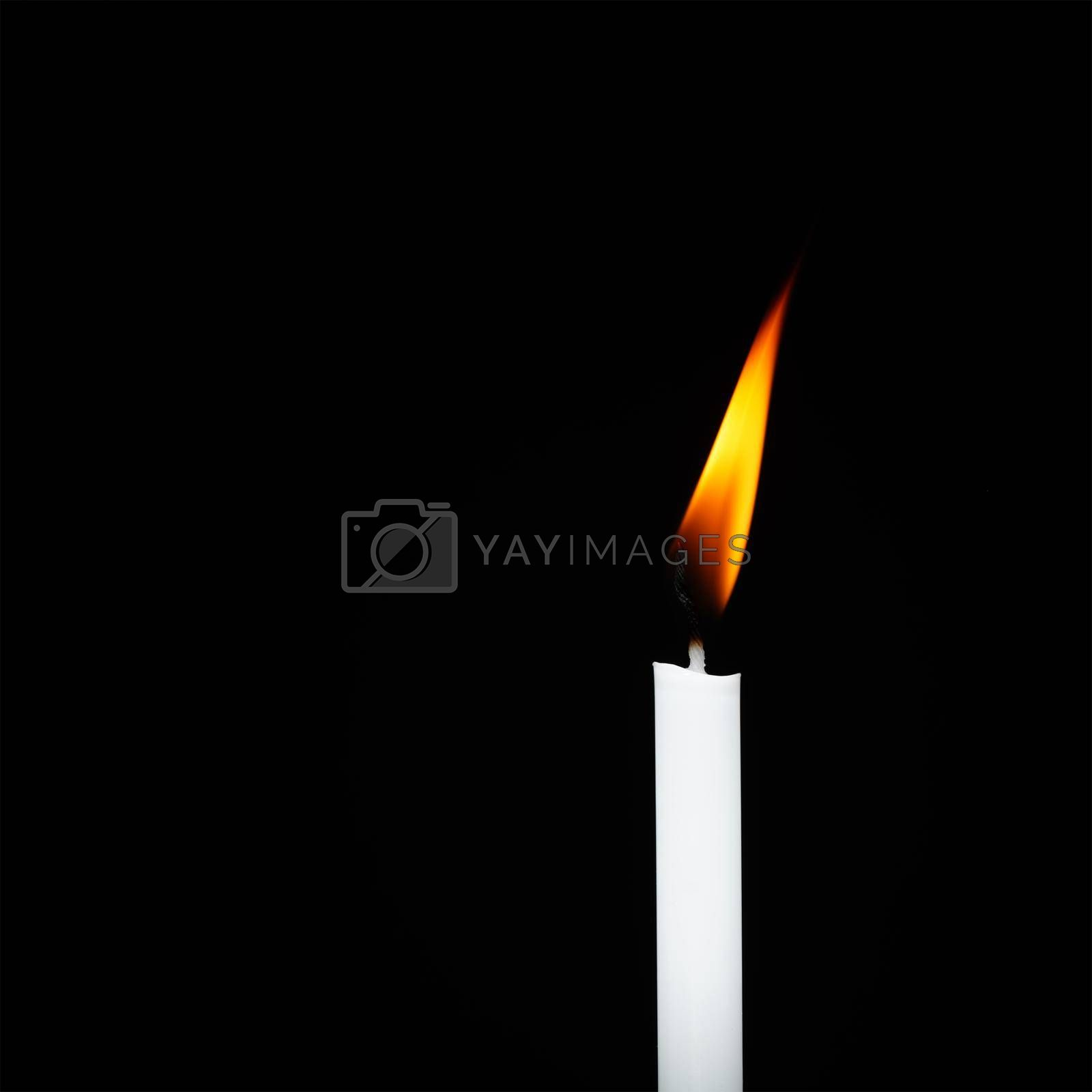 White candle flame isolated on black background religious concept belief and peace.