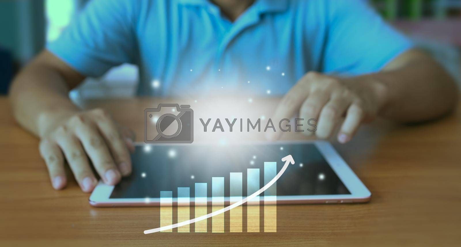 Royalty free image of The hand of an enterprise employee using a tablet to analyze business data. Corporate growth concept Development and creation of sustainable goals. by noppha80