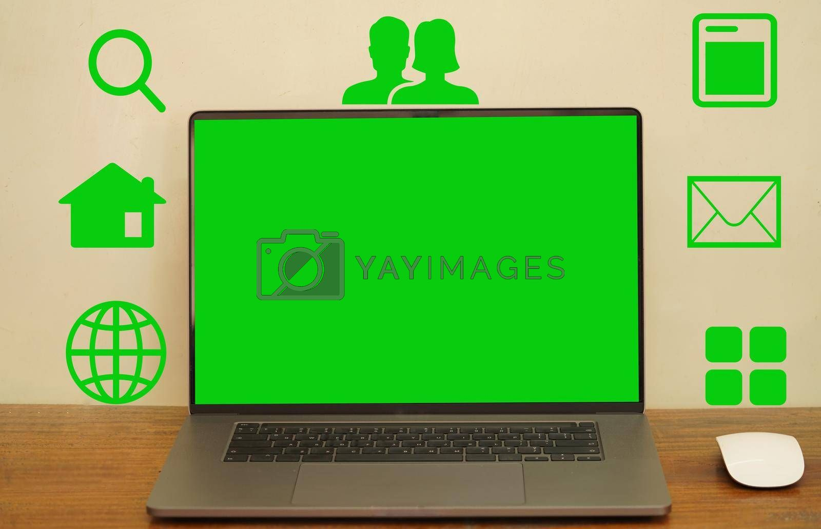 An abstract green screen laptop and mouse placed on a long desk with icons showing symbols to take advantage of the various programs.