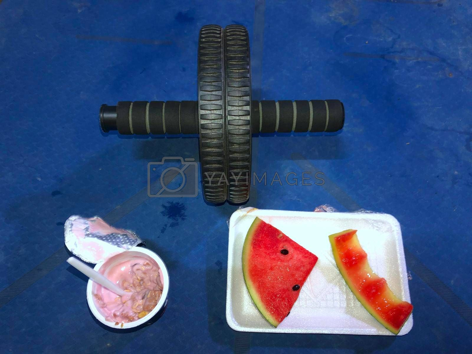 Royalty free image of Yogurt and watermelon Upper-specific exercise rolling wheel blue yoga mat sectional exercise concept And healthy eating. by noppha80