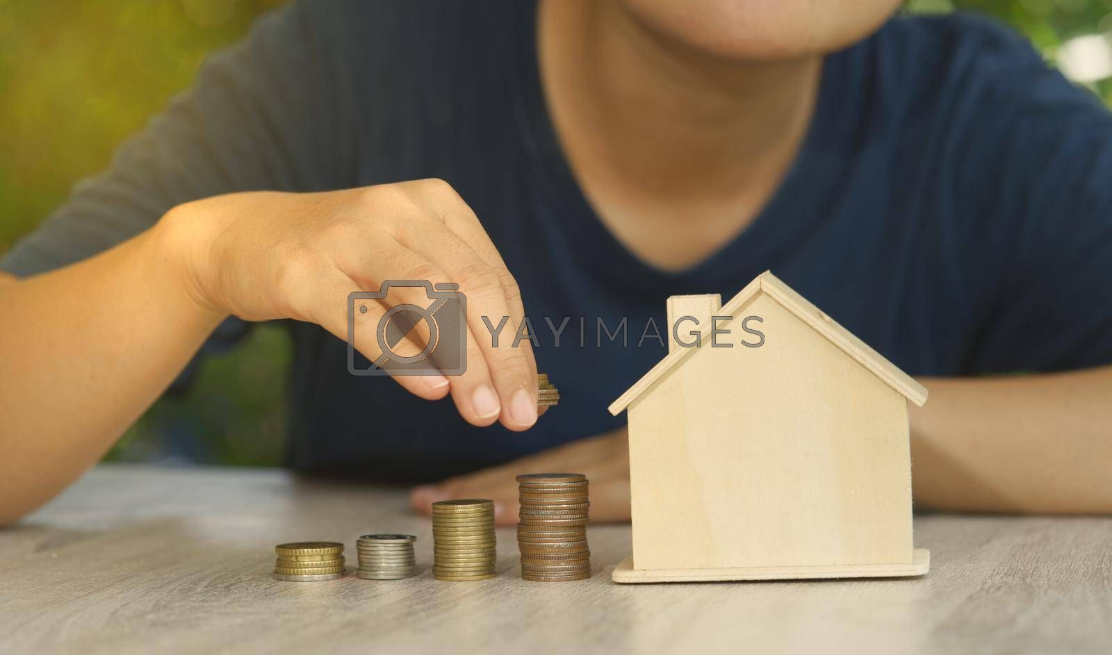 Abstract Investor puts coins stacked on the desk with mockup house concept auction value real estate investment wealth financial investment and business income growth.
