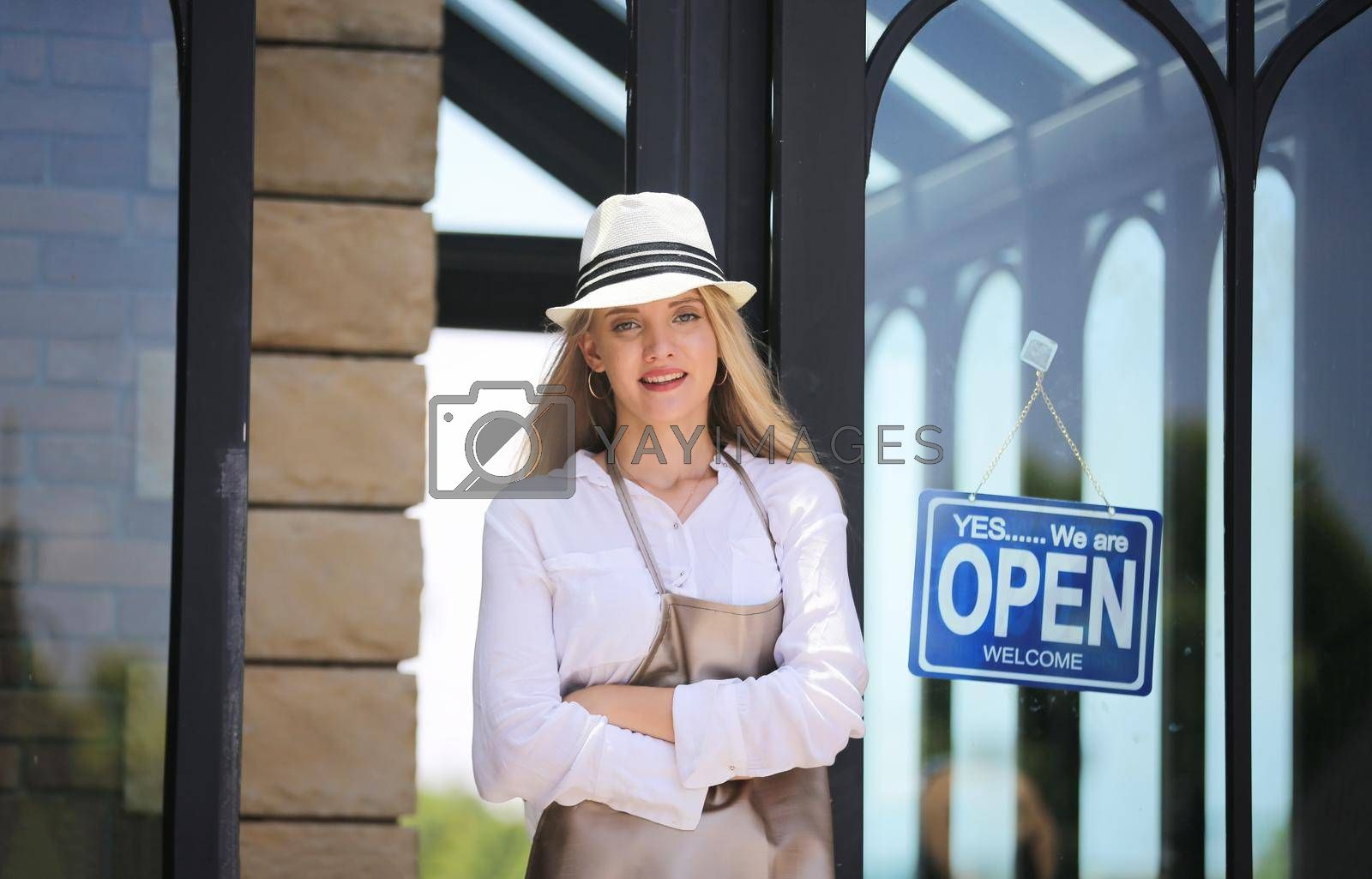 Beautiful blonde hair girl standing by open shop sign plate at door with confidence in front of coffee shop.
