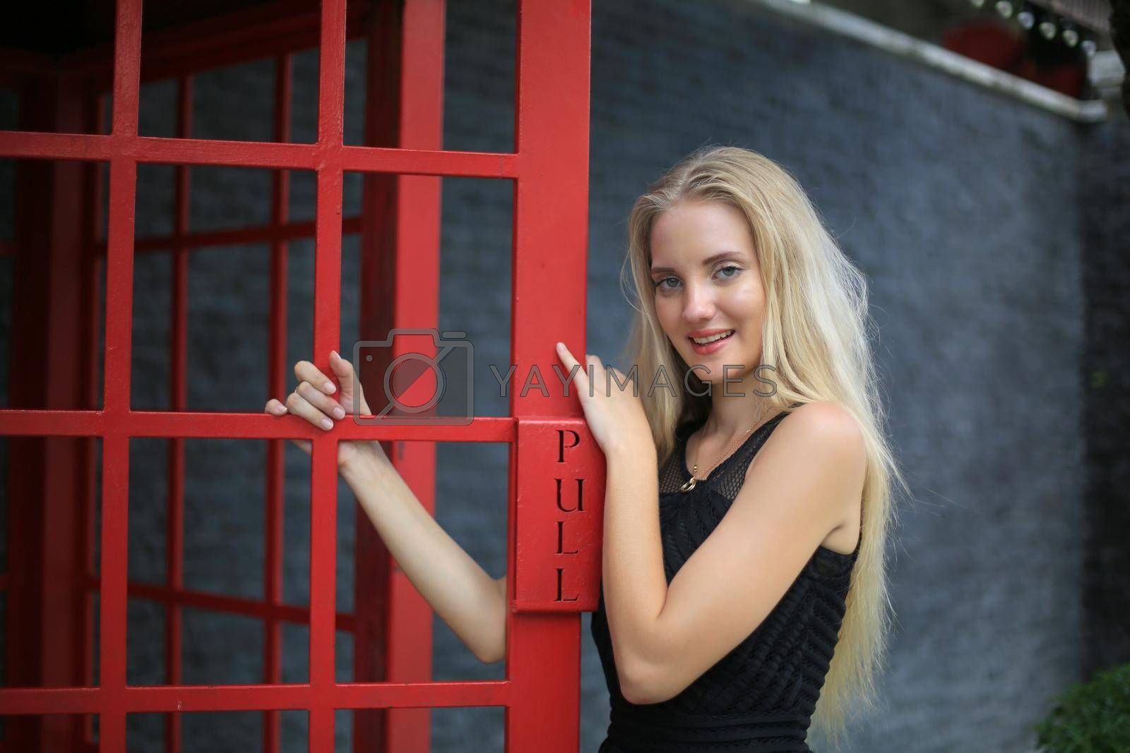 Portrait of Beautiful blonde hair girl on black dress standing in red phone booth against black wall as portrait fashion pose outdoor.