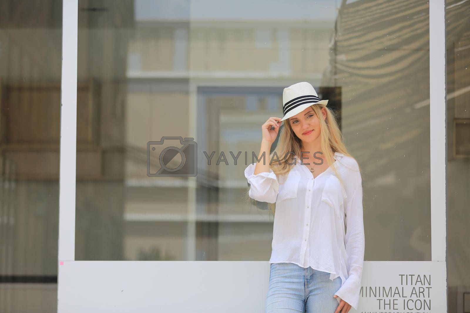 Beautiful blonde hair girl with white hat standing against wall glass as fashion pose outdoor.