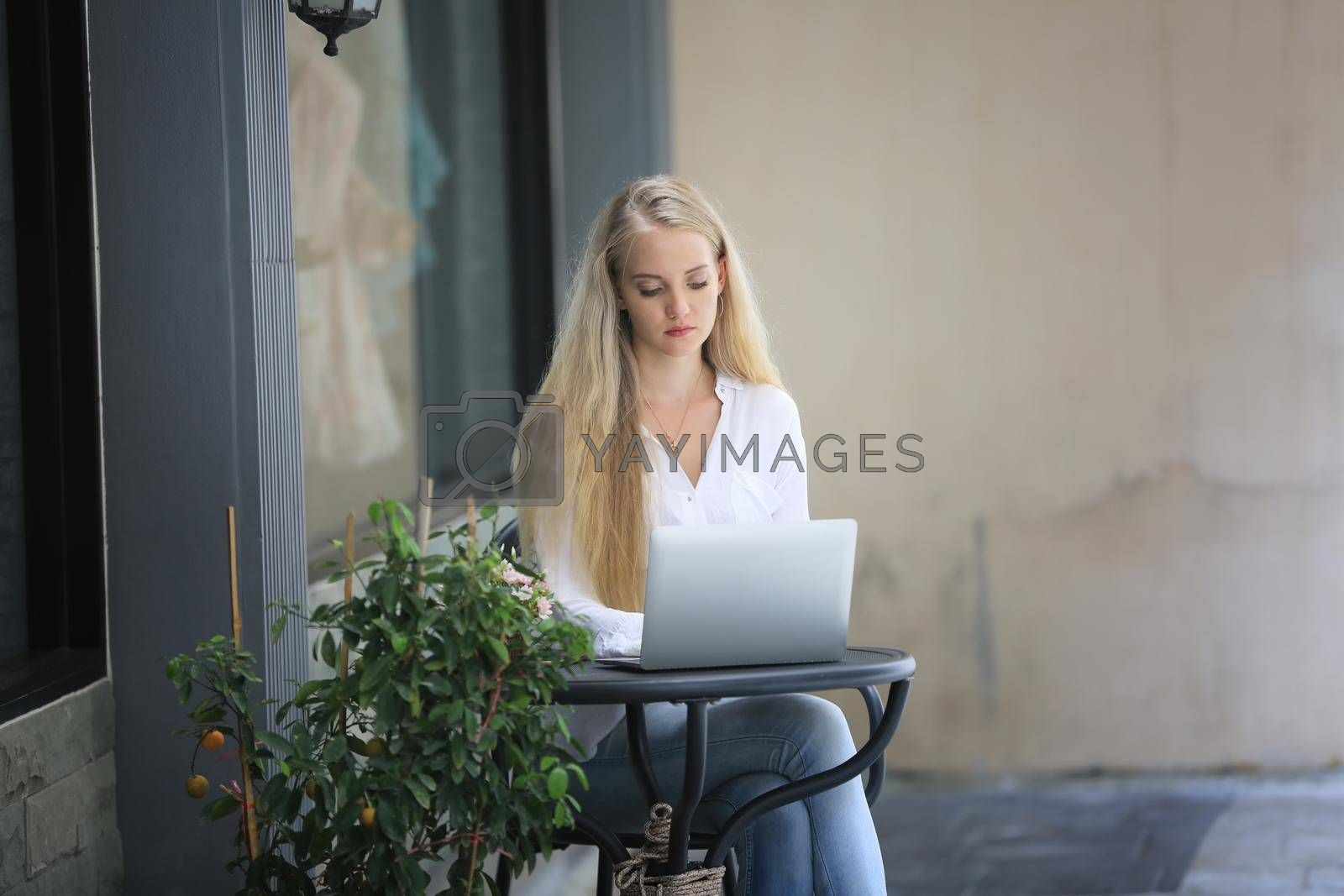 Beautiful blonde hair girl sitting with laptop in front of retails shop,Small business owner concept