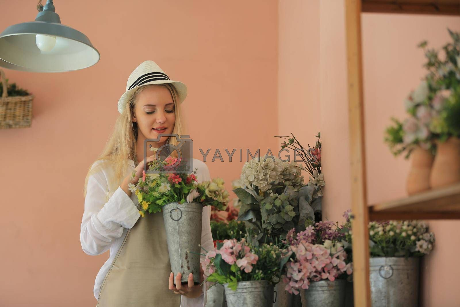 Beautiful blonde hair girl standing with confidence in front of flower in open retails flora shop. Small business owner concept.