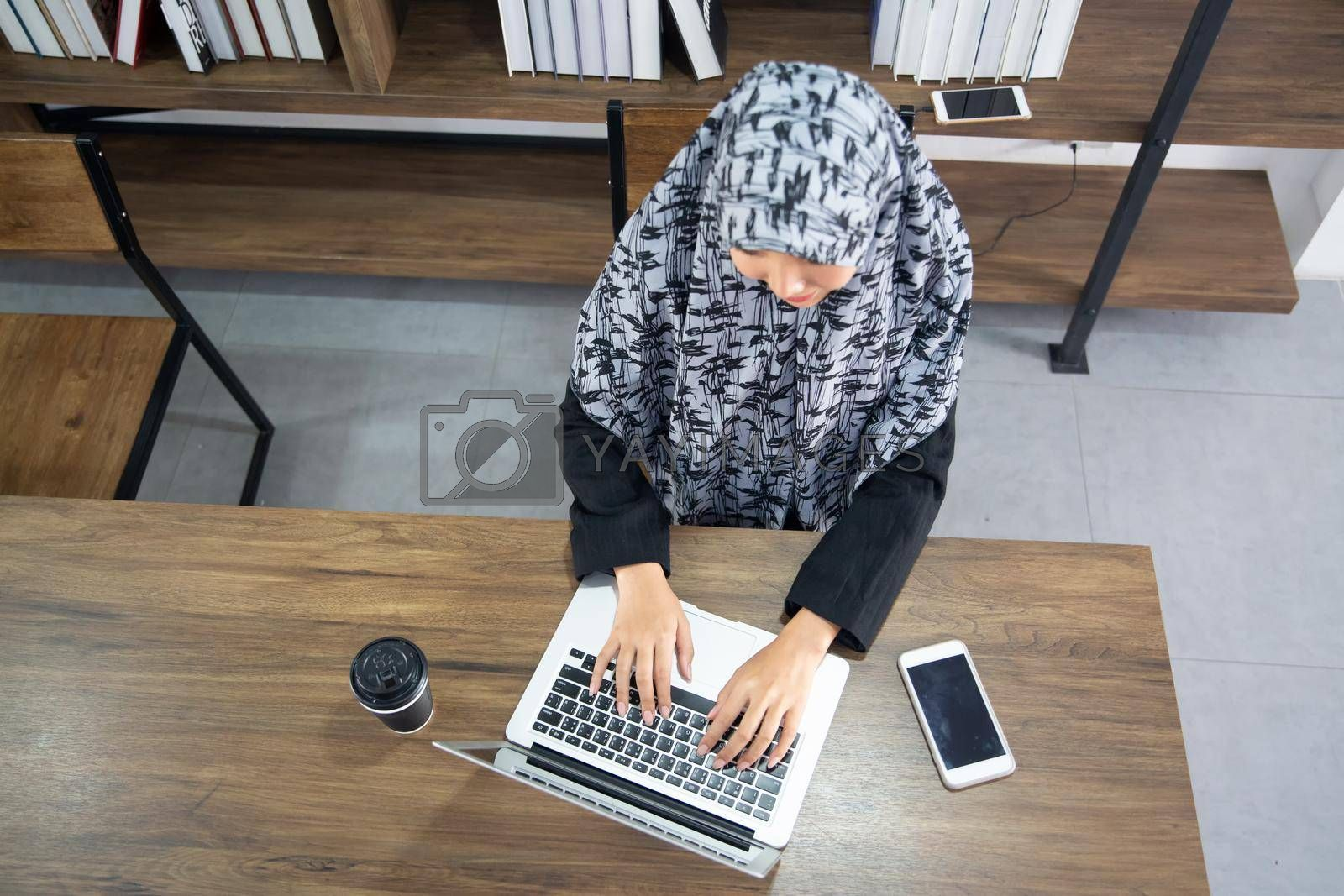 Royalty free image of young Muslim woman using a laptop in a modern office by chuanchai