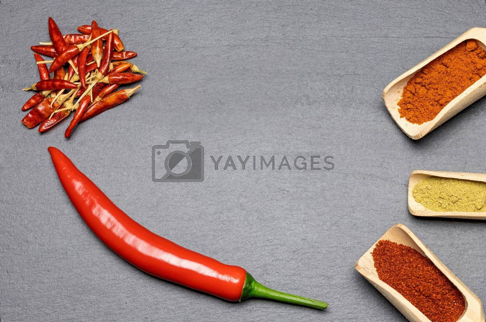Royalty free image of Fresh, dried and ground chili on the desk. by Frank11
