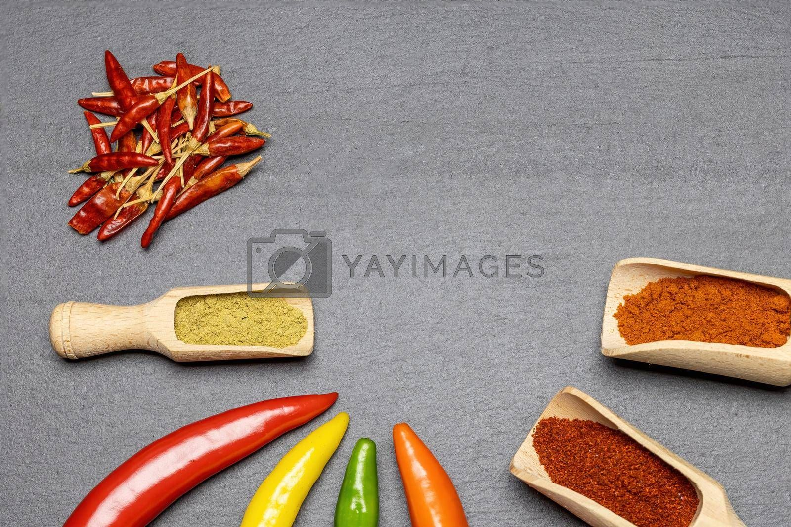 Royalty free image of Multicolored fresh chilli peppers and dried and ground chilli on the desk. by Frank11