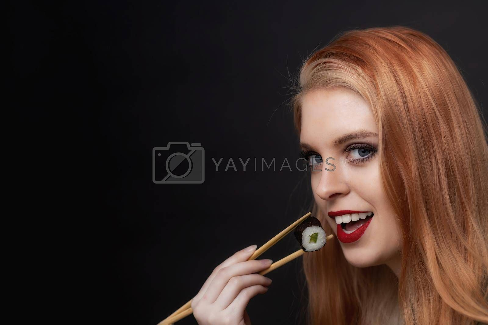 Royalty free image of Side view portrait of young woman tasting sushi closeup. by Frank11