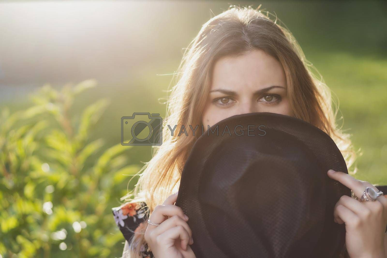 Royalty free image of Portrait of beautiful girl hiding her face behind hat. by Frank11