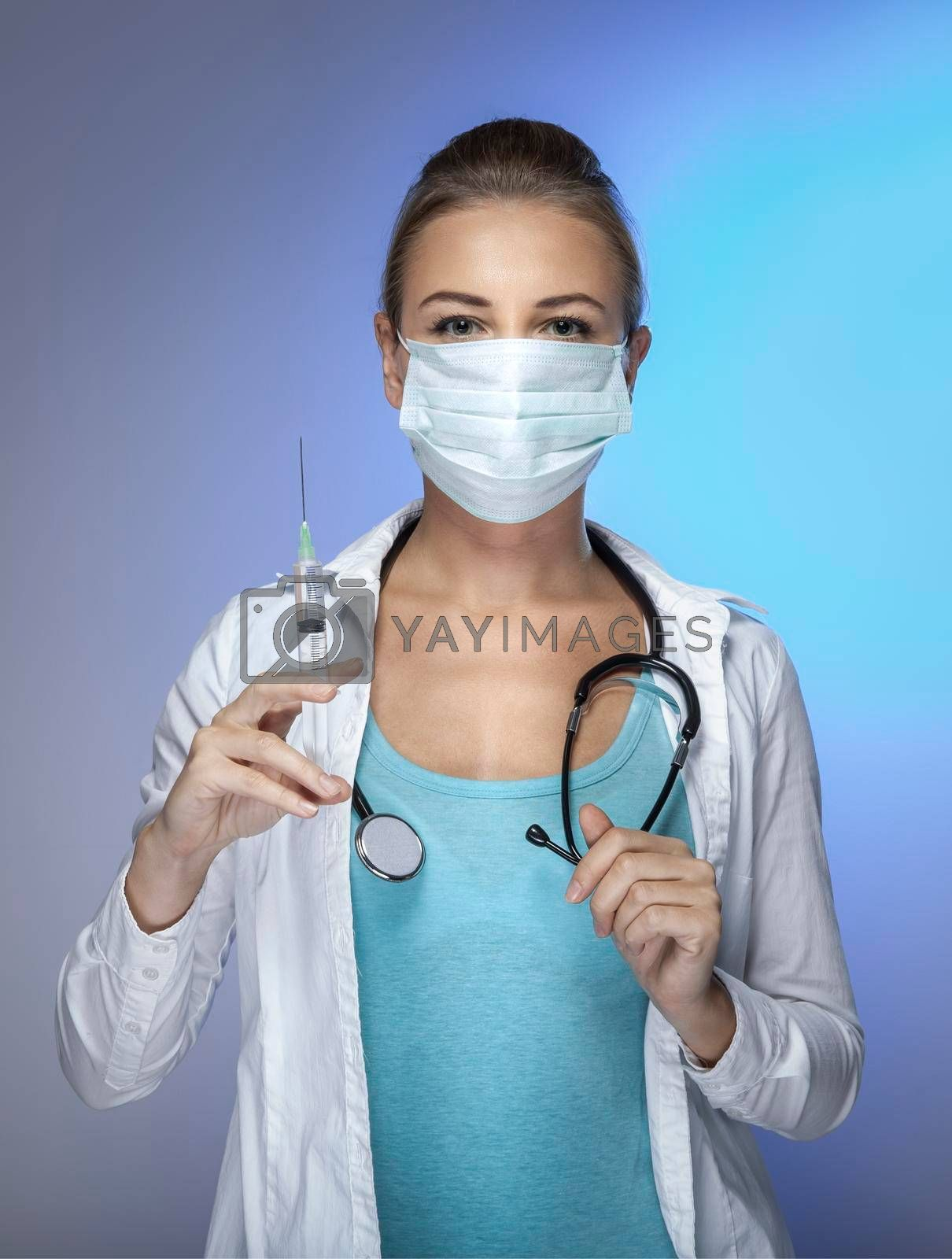 Portrait of a Doctor Wearing Mask with Syringe in Hand isolated on Blue Background. Beauty Treatment. Injection of Beauty. Women's Beauty.