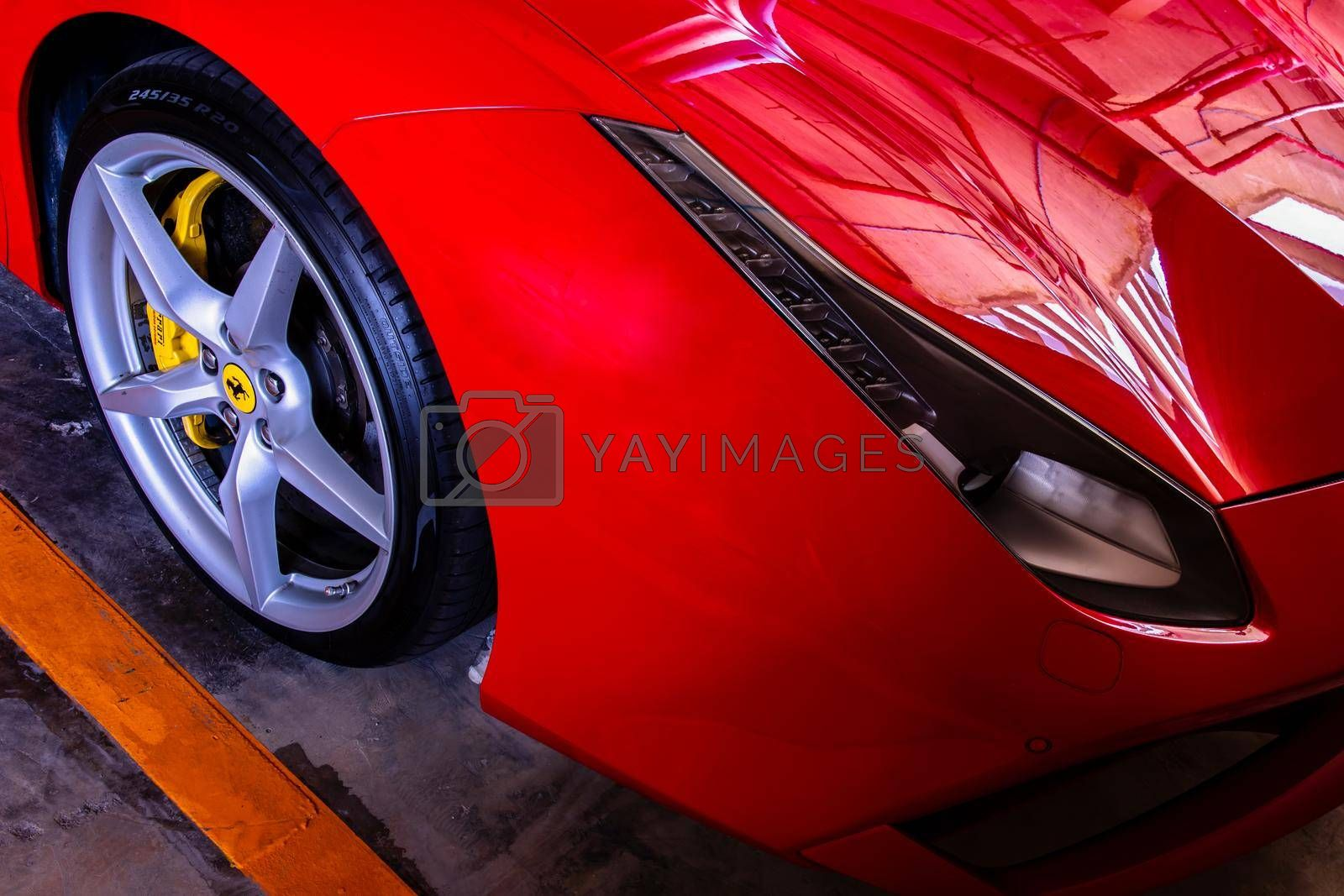 Bangkok, Thailand - 06 Jun 2021 : Close-up of Headlights, Wheel, and Rim of Red metallic Ferrari car. Selective focus.