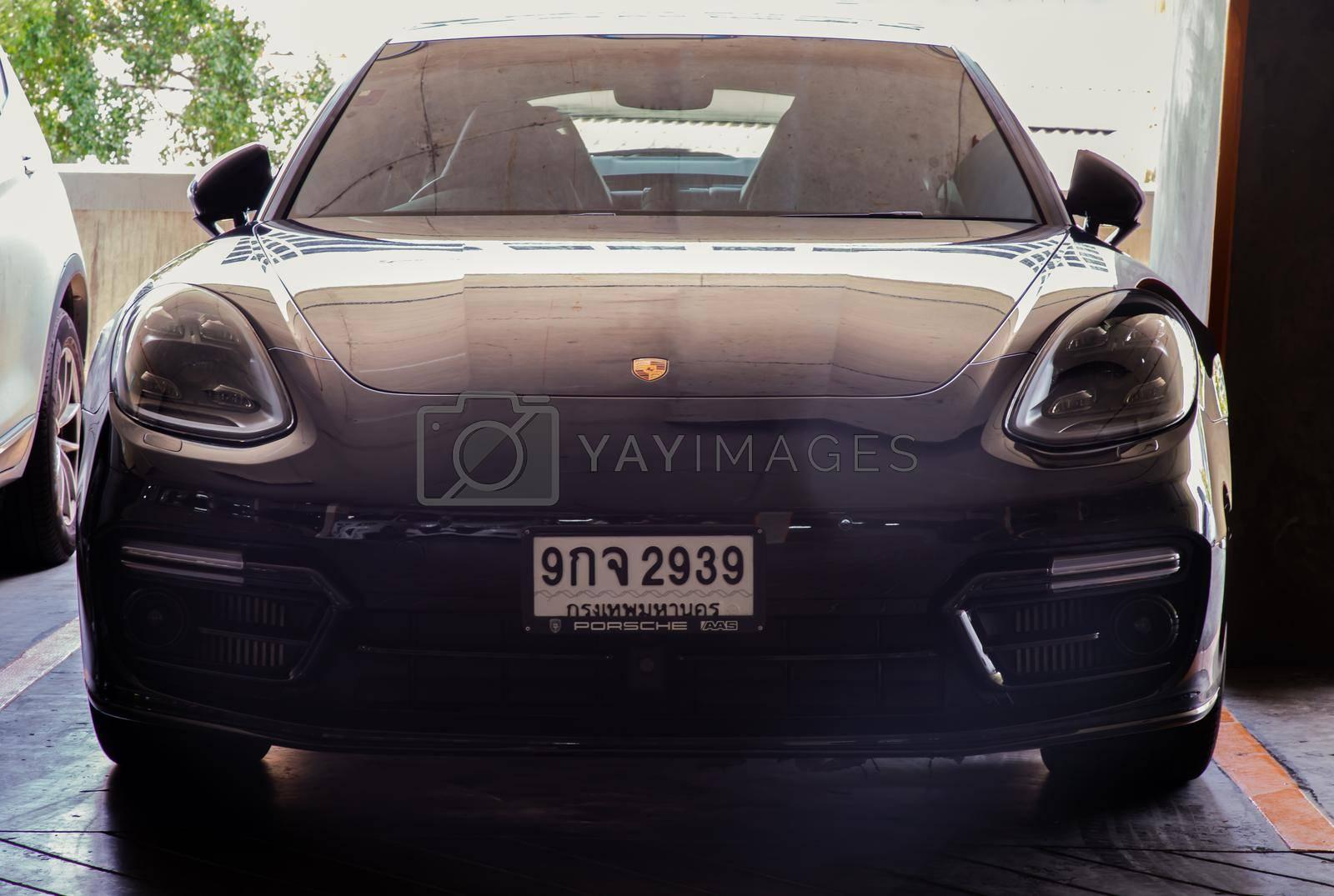 Bangkok, Thailand - 06 Jun 2021 : Front view shot of Black porsche sports car parked in the parking lot. Selective focus.