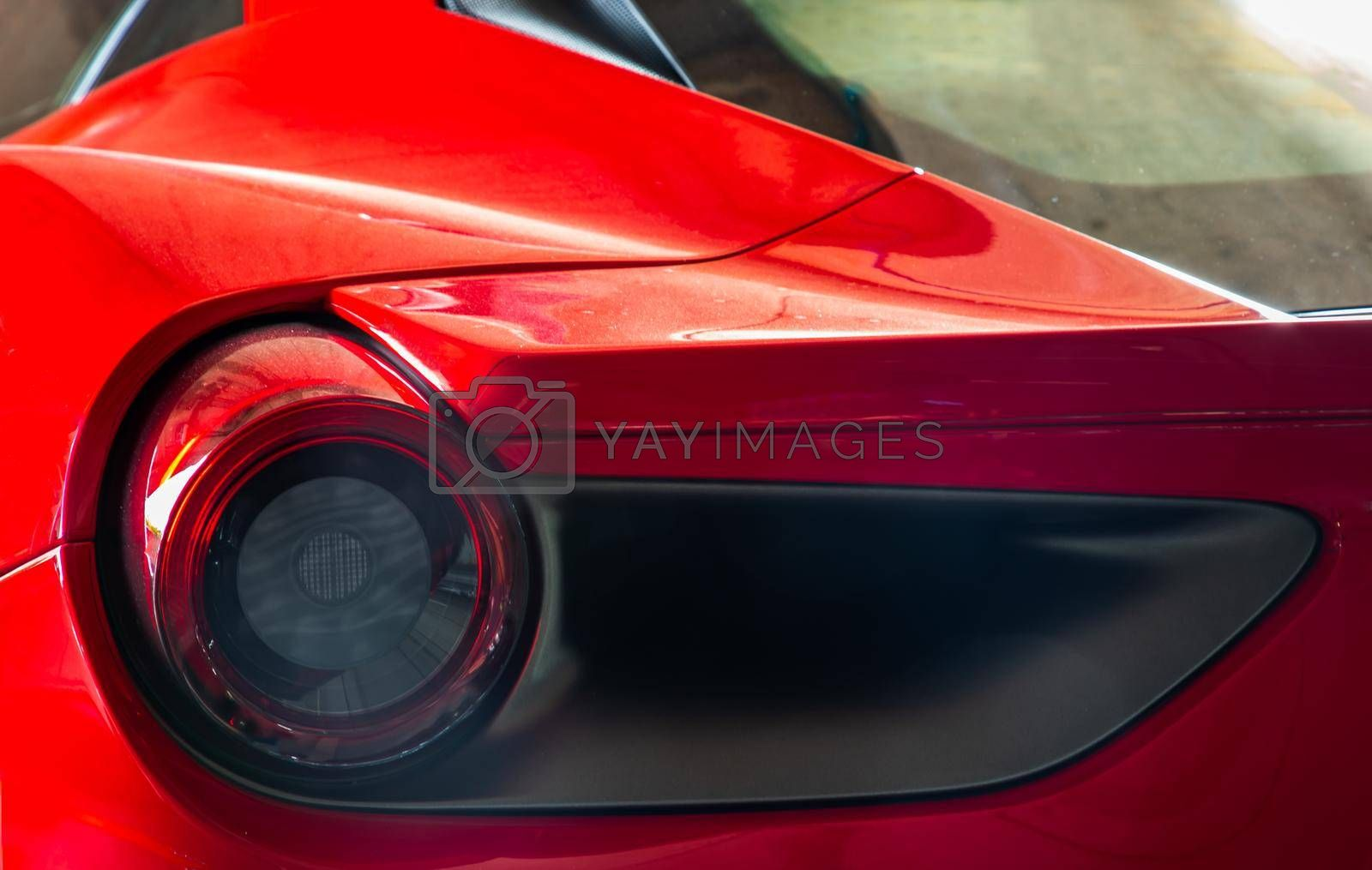 Bangkok, Thailand - 06 Jun 2021 : Close-up of Rear light or Tail lamp and Rim of Red ferrari car. Ferrari is Italian sports car. Selective focus.