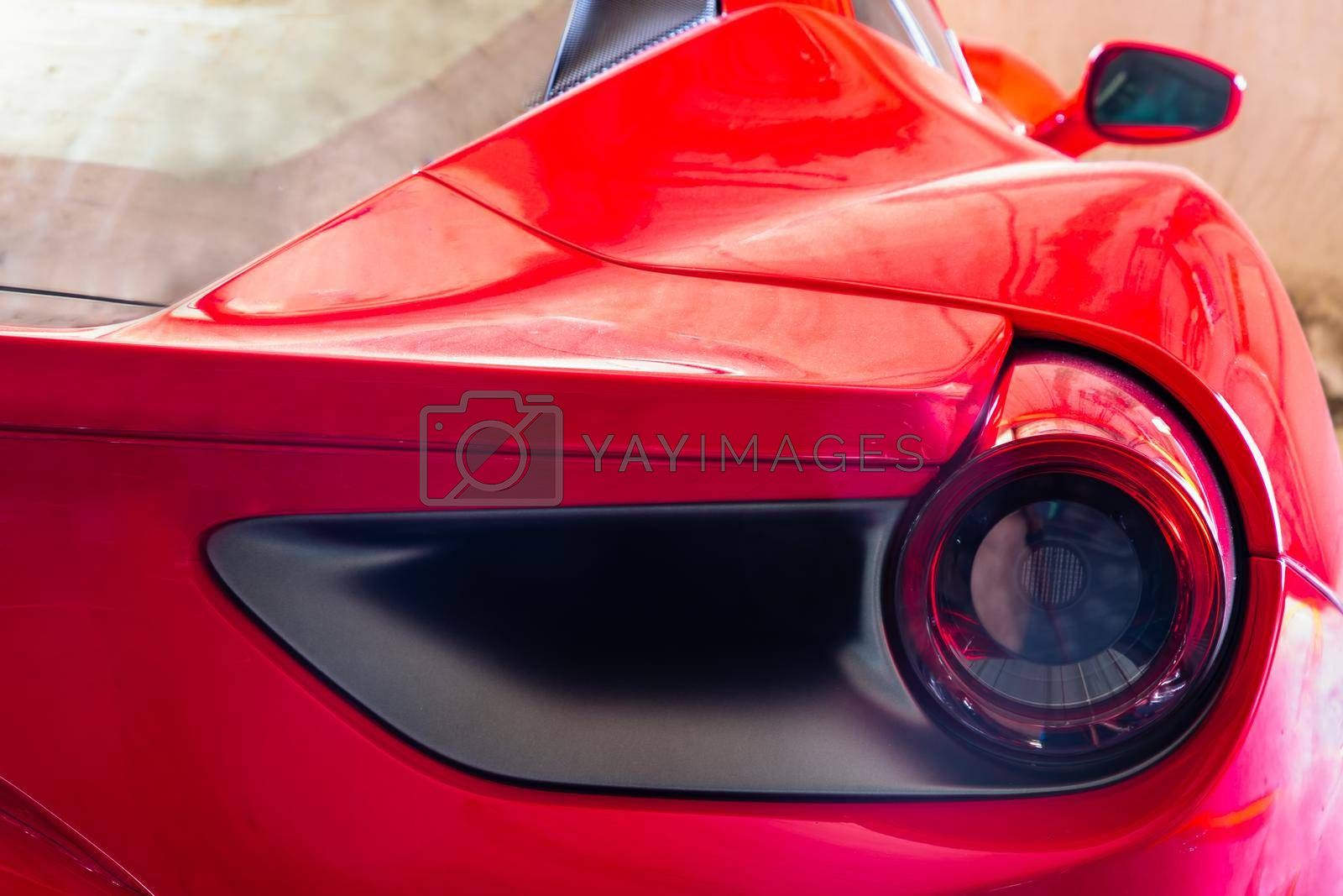 Bangkok, Thailand - 06 Jun 2021 : Close-up of Rear light or Tail lamp and Side view mirror of Red ferrari car. Ferrari is Italian sports car. Selective focus.