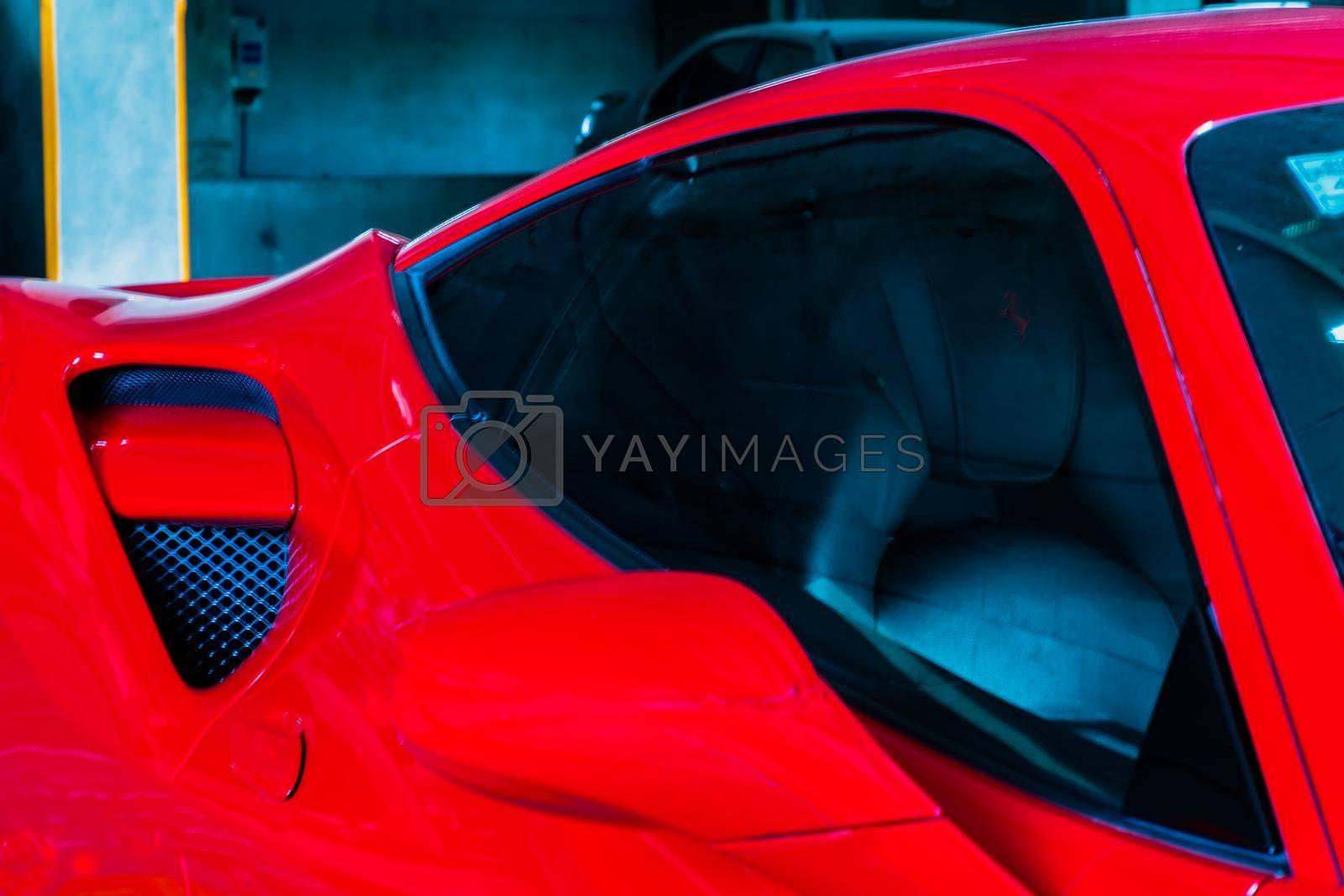 Bangkok, Thailand - 06 Jun 2021 : Close-up of Side Mirror and Car window of Red ferrari car. Ferrari is Italian sports car. Selective focus.