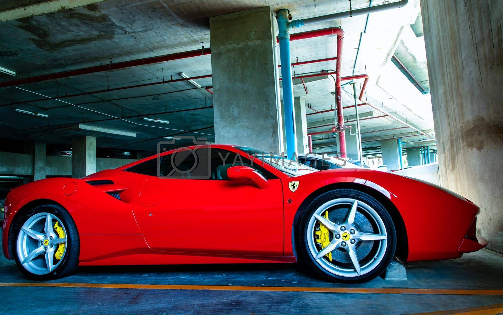 Bangkok, Thailand - 06 Jun 2021 : Side view of Red metallic Ferrari car in the parking lot. Ferrari is Italian sports car. Selective focus.