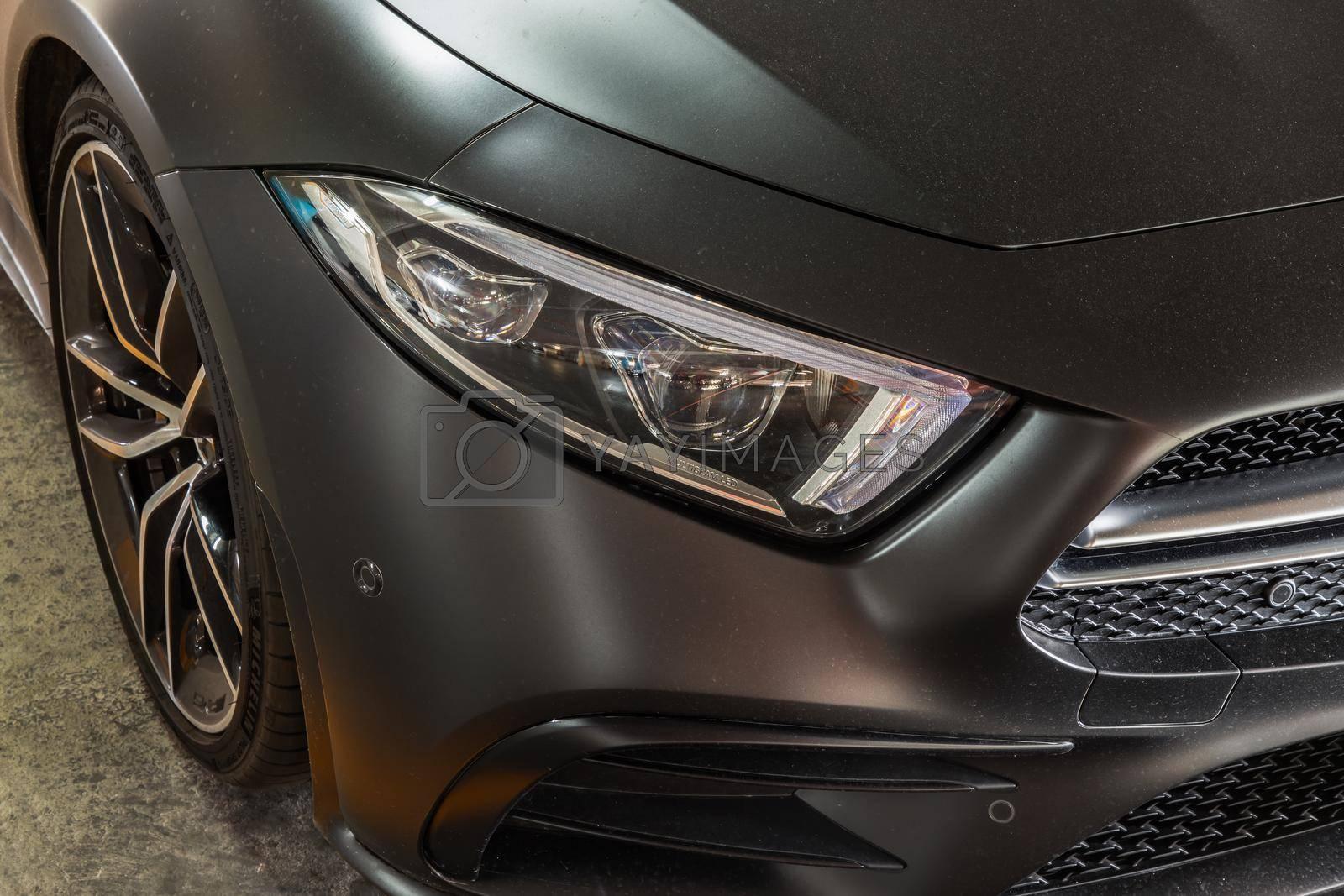 Bangkok, Thailand - 08 Jun 2021 : Close-up of Headlights, Wheel, and Rim of Matte black mercedes sports car. Selective focus.
