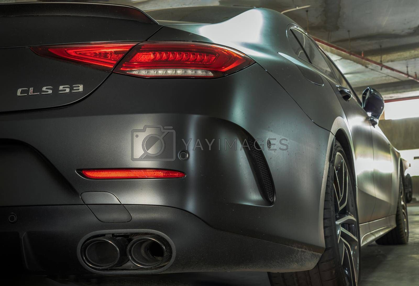 Bangkok, Thailand - 08 Jun 2021 : Close-up of Rear light or Tail lamp, exhaust pipe and Wheel of Matte black mercedes sports car parked in the parking lot. Selective focus.