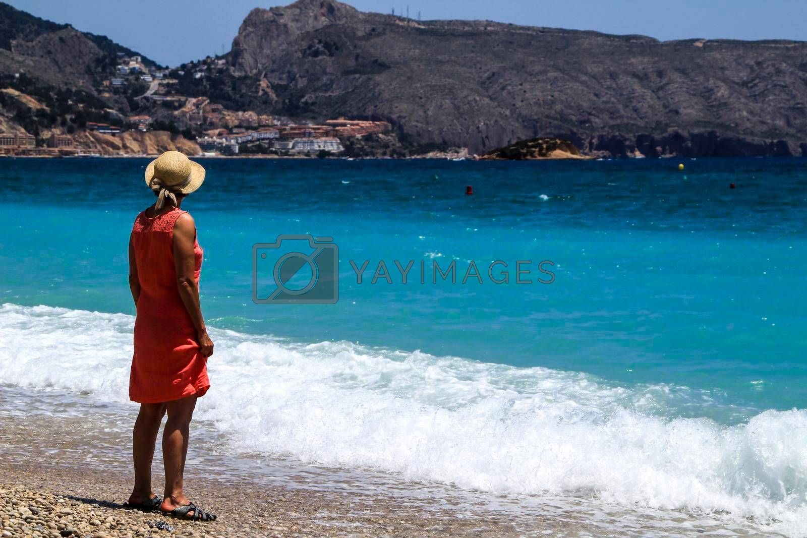Woman in red dress and hat on Cap Negret beach on a sunny day of Spring in Altea, Alicante, Spain