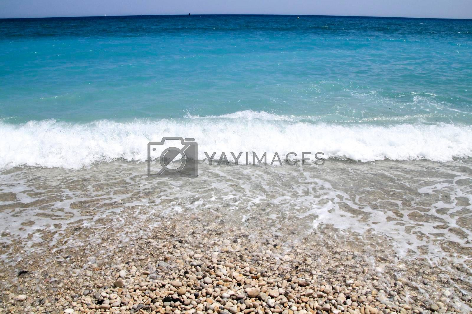 Blue wavy sea and pebbles shore in the morning in Cap Negret beach in Altea