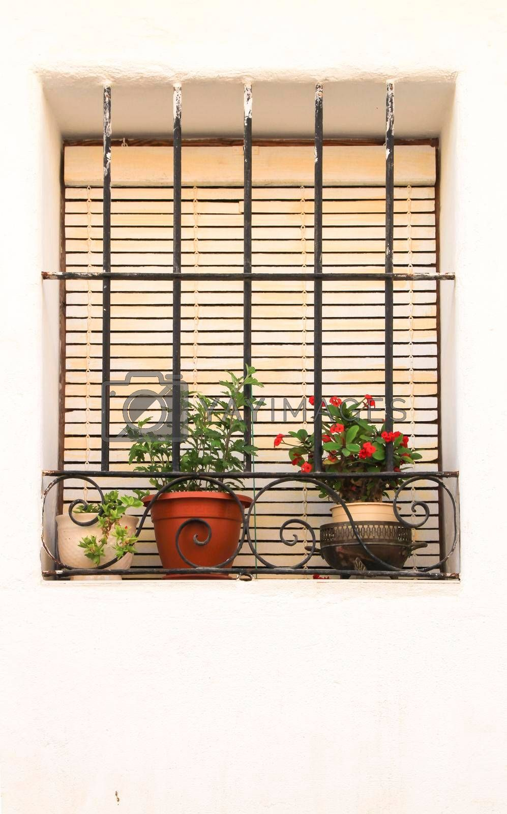 Whitewashed facade with window with forged metal grill in Altea village, Alicante, Spain