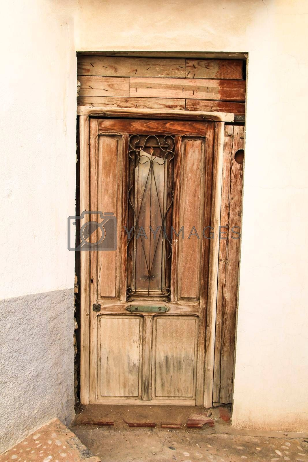 Whitewashed facade with old wooden door with iron details in Altea village, Alicante, Spain