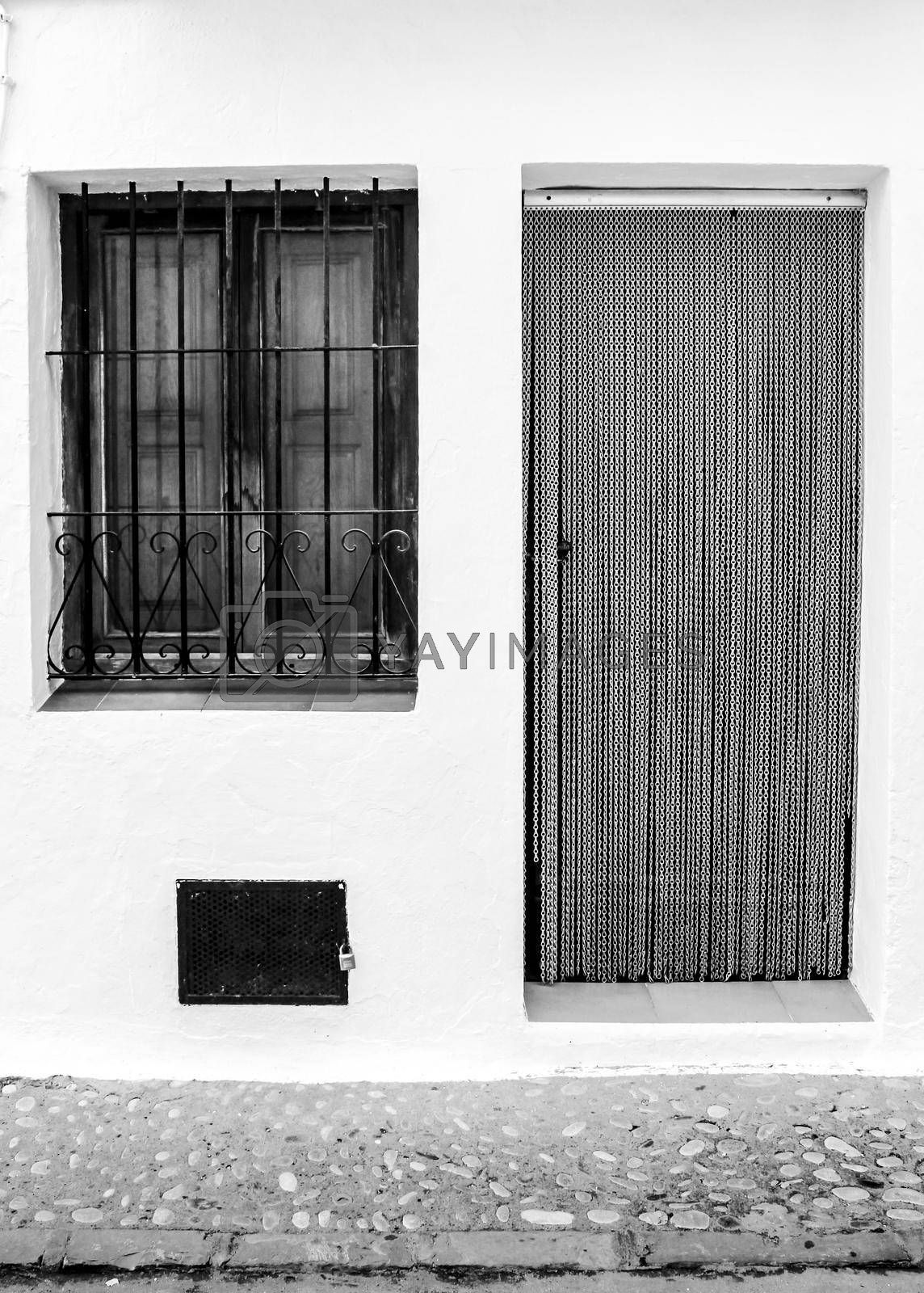 Striped metal curtain on door and window with metal grill of a village house in Altea, Alicante, Spain