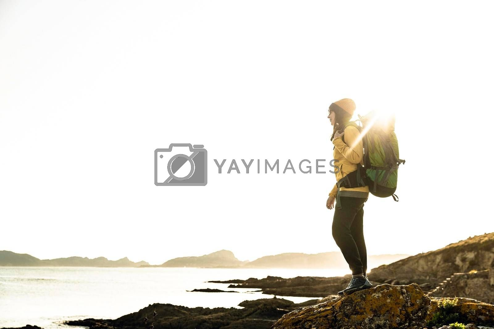 Royalty free image of Woman exploring the coastline with backpack by Iko