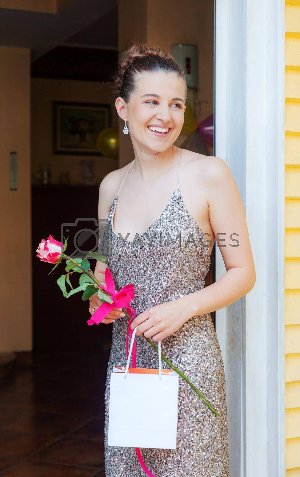 Royalty free image of Happy Girl Graduate is Standing on the Porch Smiling Holding Empty Bag and Rose by vilevi
