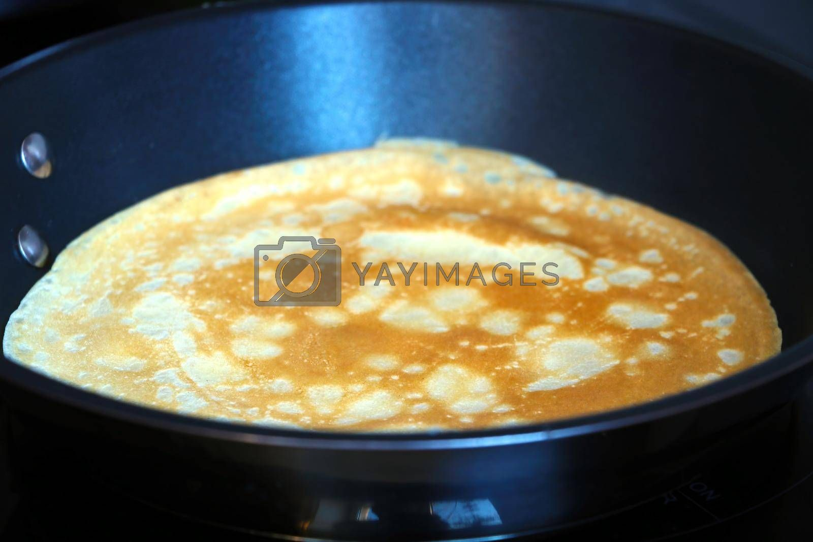 Royalty free image of Prepare a pancake in a skillet. Light and pleasant breakfast. Homemade food. by kip02kas