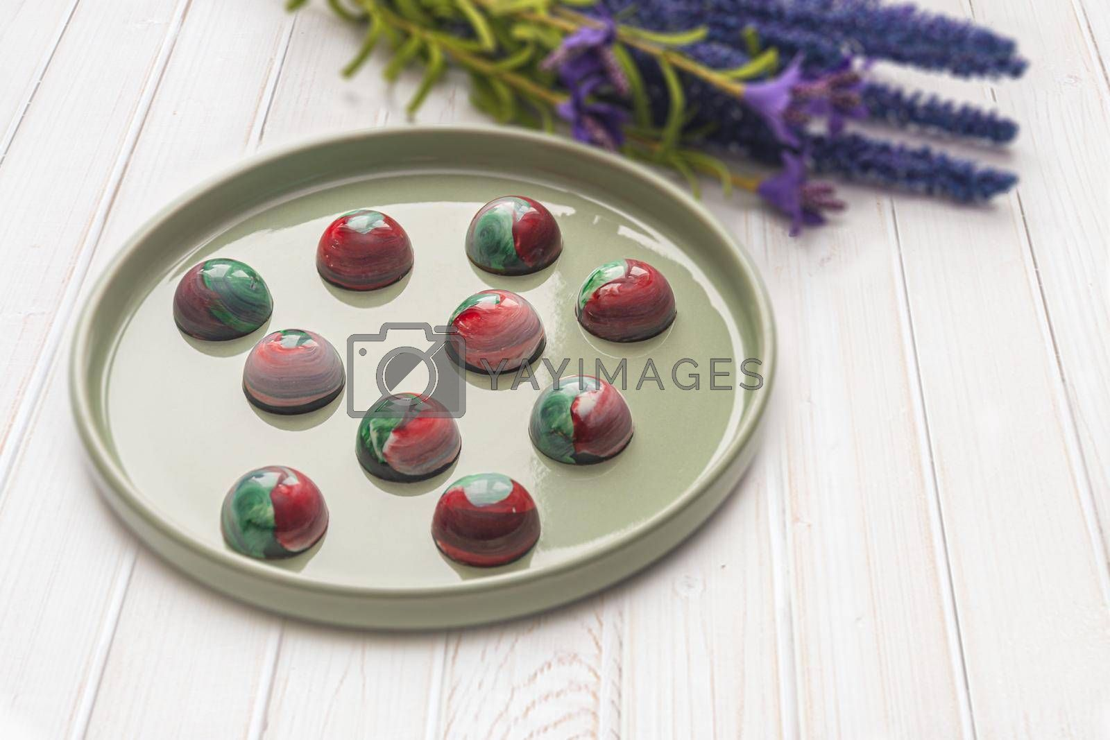 Collectible handmade tempered chocolate candies with a glossy painted body on a round plate with a blurred background and bokeh elements. Stock photography.