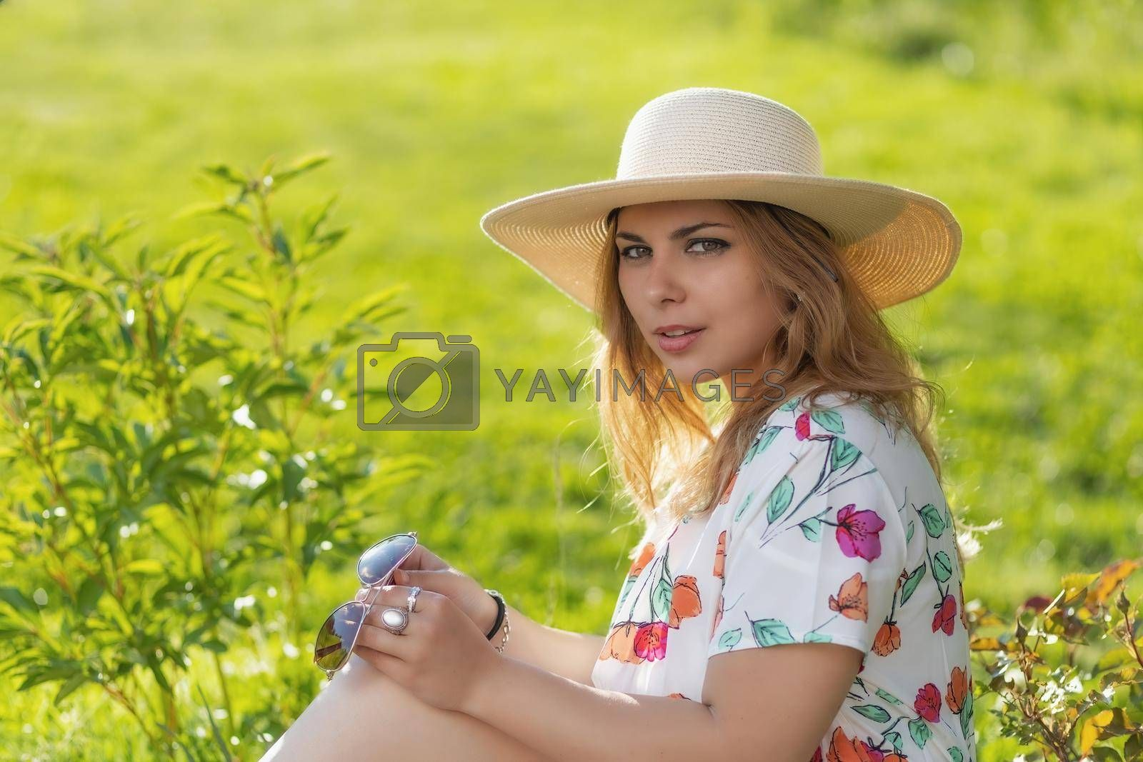 Royalty free image of Portrait of attractive  young woman in straw hat posing outdoors. by Frank11