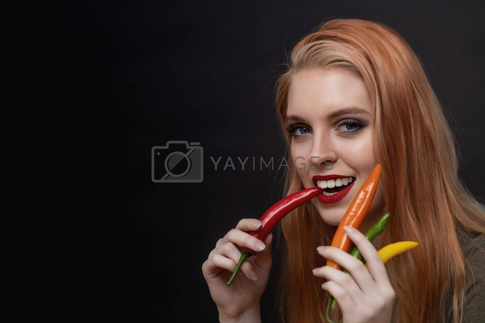 Royalty free image of Attractive young woman is tasting red chili pepper by Frank11