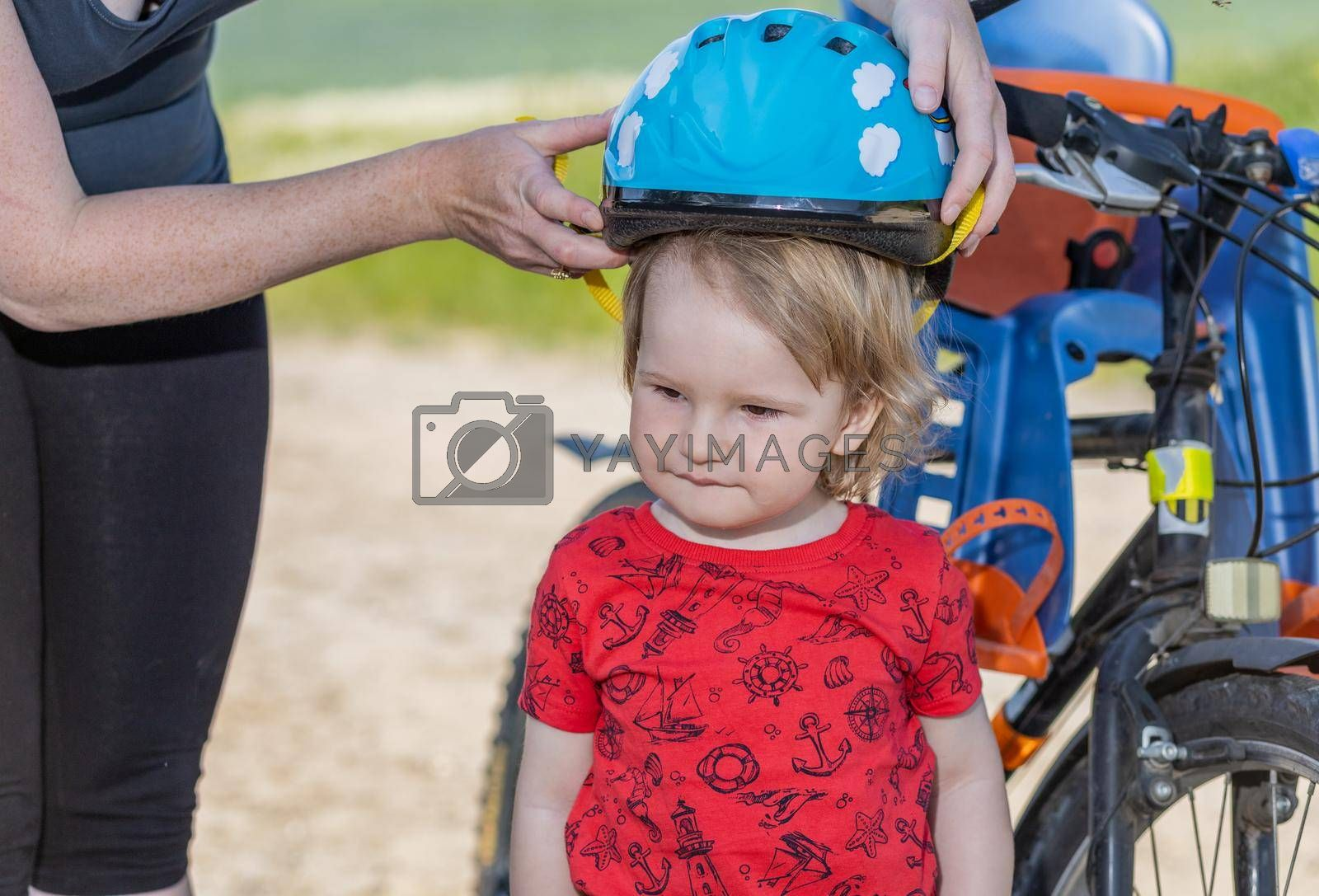 Royalty free image of Mother puts on the  head of little boy safety helmet by Frank11