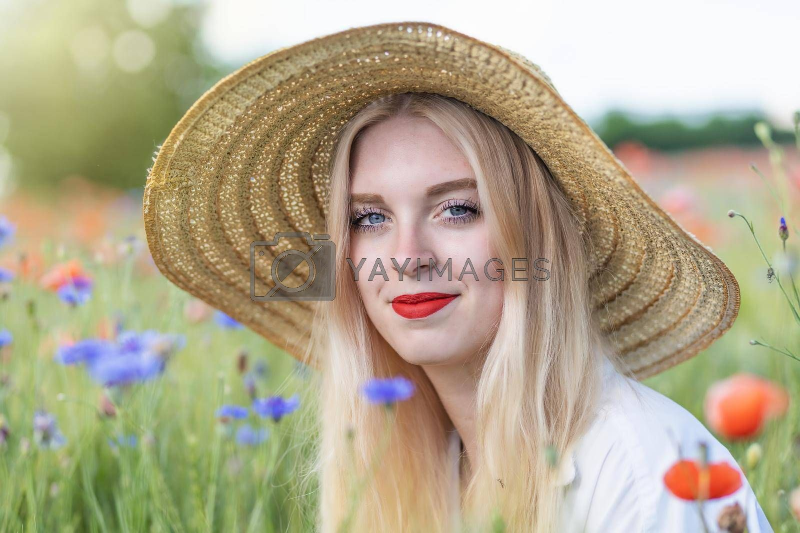 Royalty free image of Portrait of beautiful  young woman in straw hat is posing  outdoors by Frank11