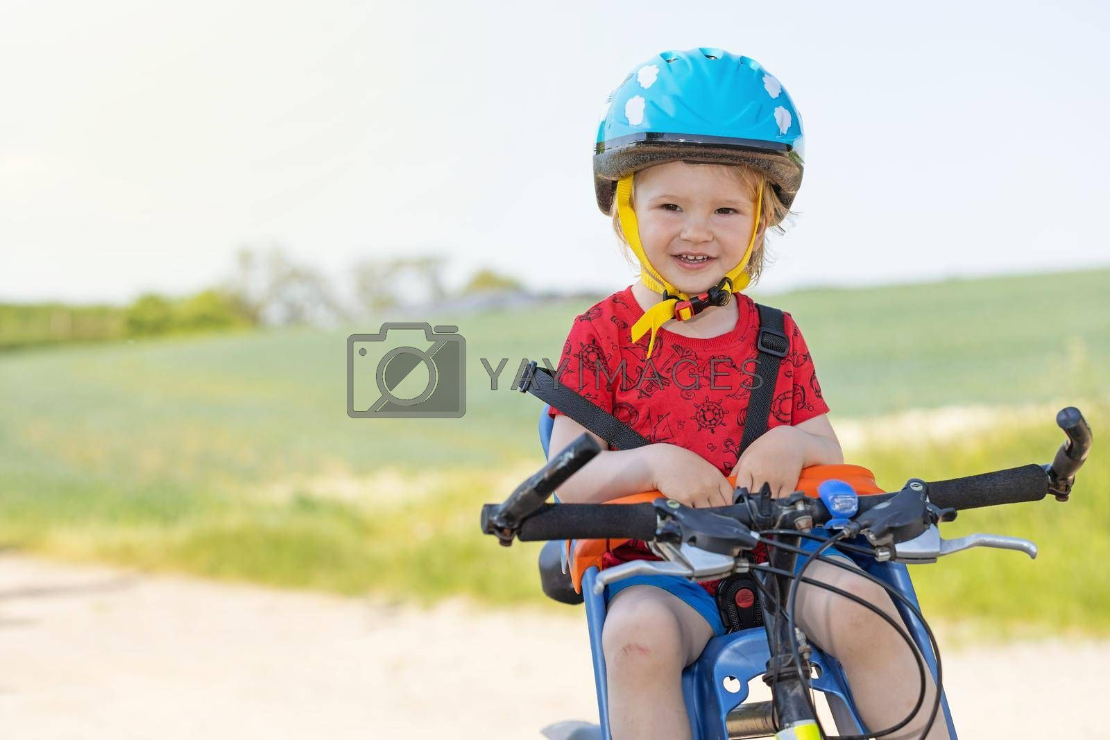 Royalty free image of Little boy with safety helmet is sitting in bicycle seat. by Frank11