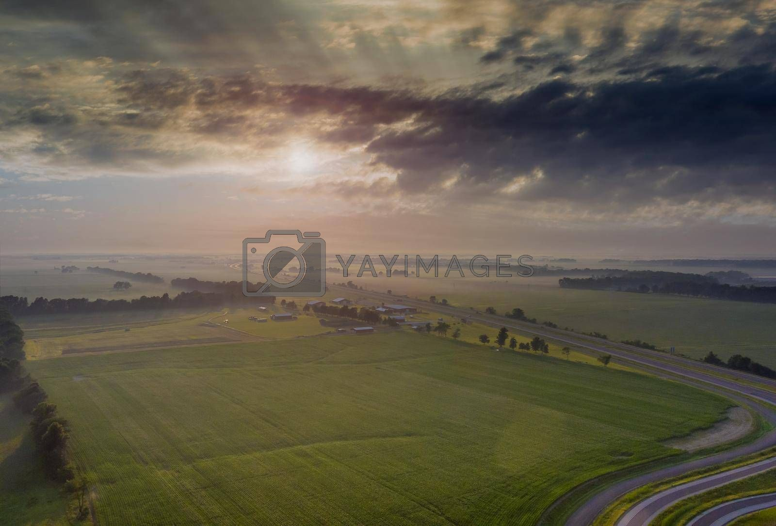 Sunrise on a field covered across high speed highway with summer season with fog and cloudy in morning of aerial view