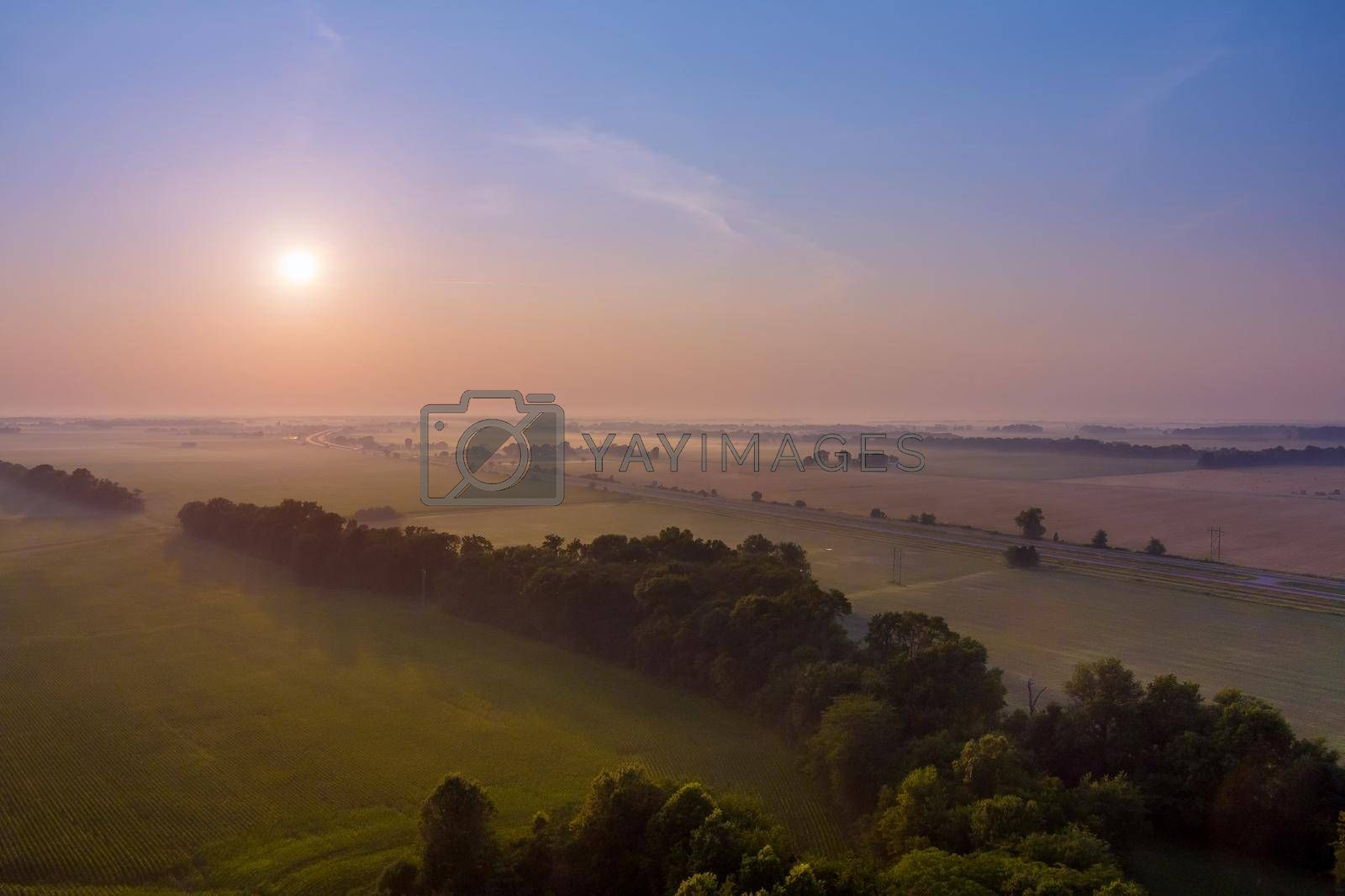 Aerial view of warm sunrise on fantastic foggy with fresh grass in the sunlight dramatic unusual scene