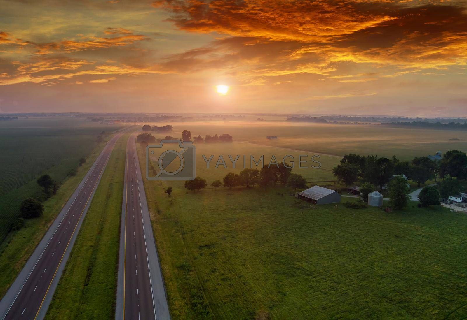 Aerial view sunrise of meadow across high speed highway on the morning in the thick fog natural landscape over the panorama landscape